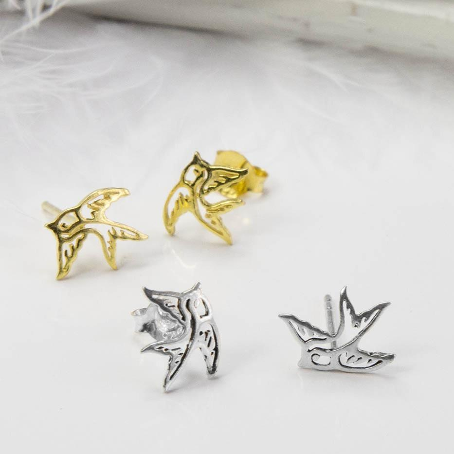 Small Gold Swallow Bird studs behind Small Silver Swallow Bird studs with white feather background