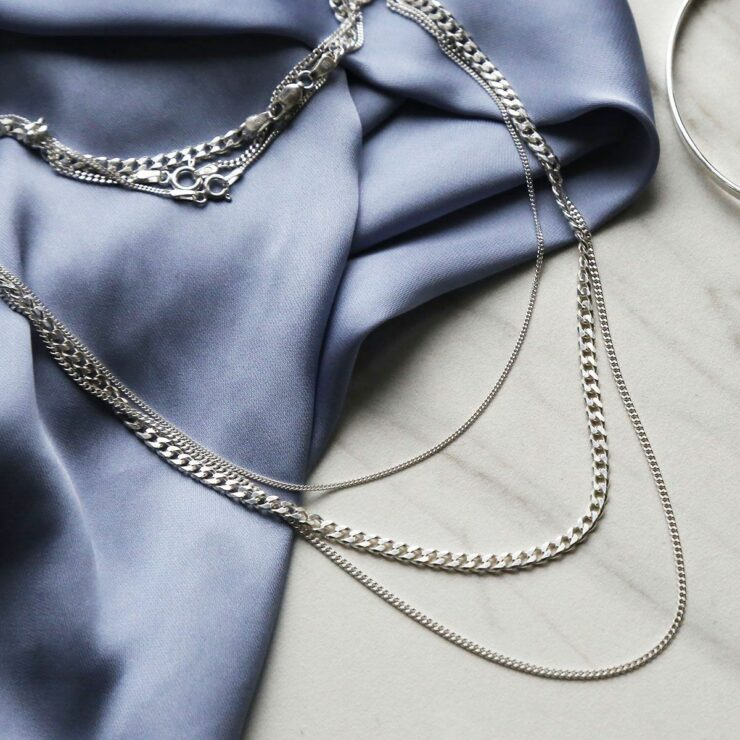 Heavy, medium and fine sterling silver curb chains on blue satin sheet