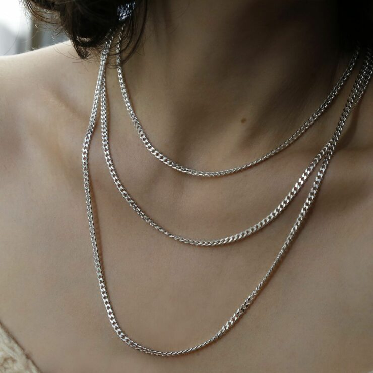 three medium snake chains layered and stacked on female model
