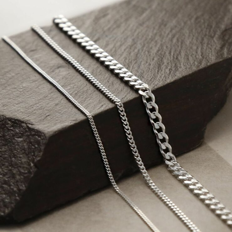 Heavy, medium and fine sterling silver curb chains on draped on wooden beam