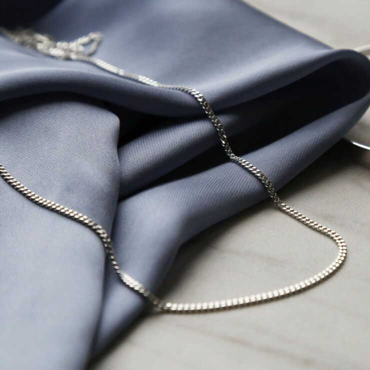 fine sterling silver curb chains on blue satin sheet