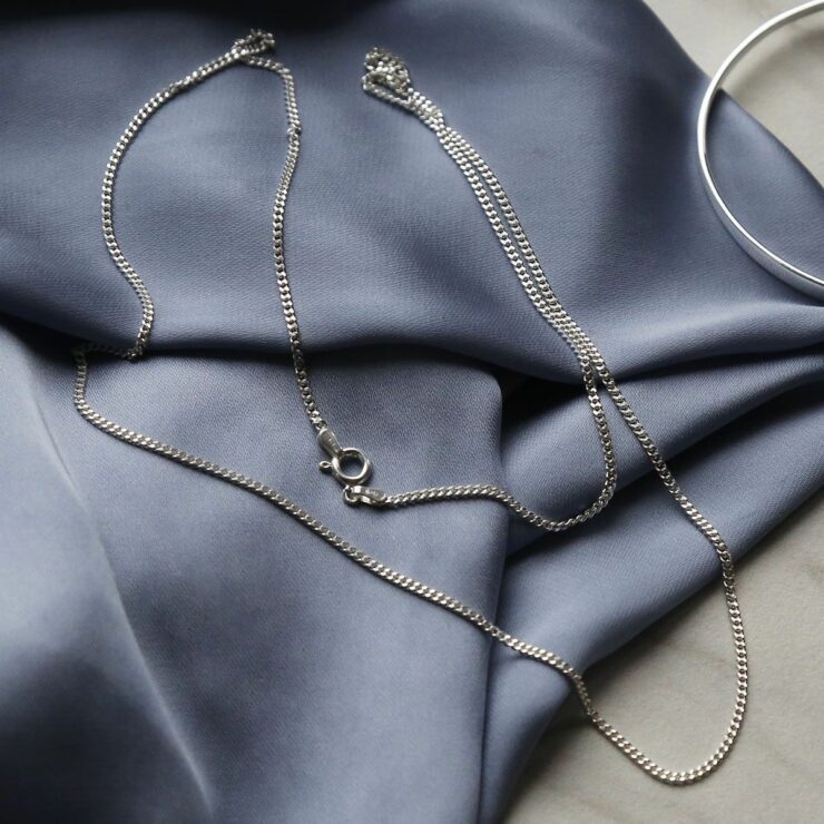fine long length sterling silver curb chains on blue satin sheet