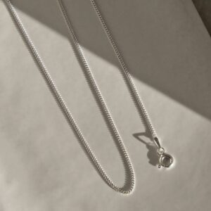 fine sterling silver curb chain on draped on white background