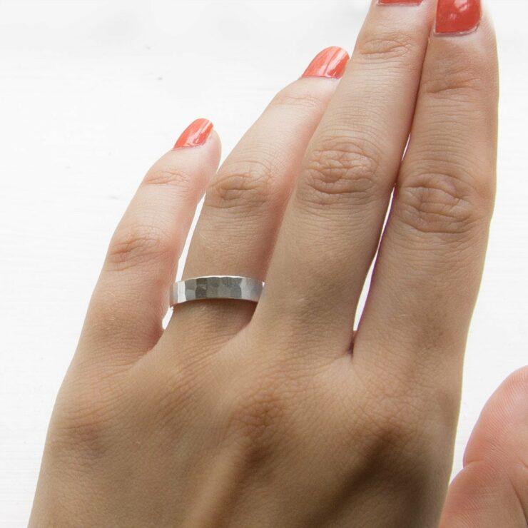 Hammered sterling silver friendship ring on model's finger.