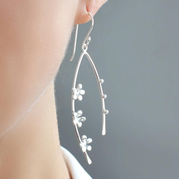 Silver arched bow earrings adorned with forget me nots