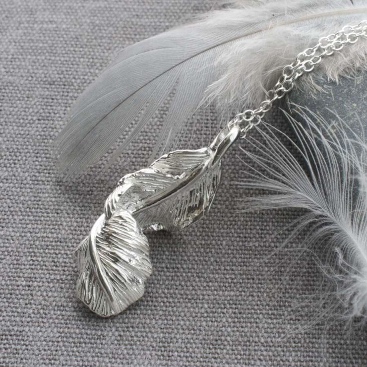 Silver furling feather pendant necklace