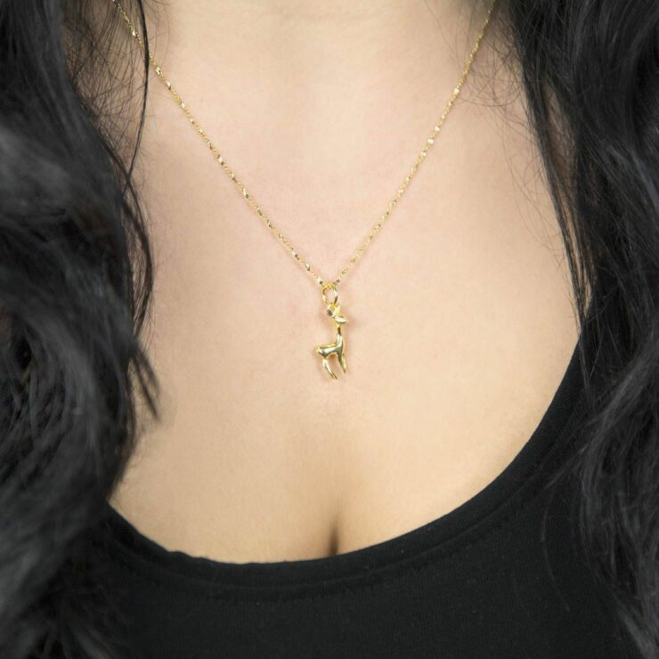 Gold deer pendant on a gold diamond cut chain hanging round a woman's neck sitting upon her chest