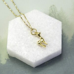 Gold deer pendant on a gold diamond cut chain with a gray background lying on a hexagonal block of marble