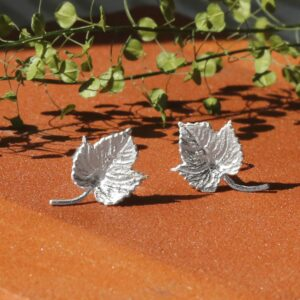 Silver Ivy Leaf Earrings with Terracotta background and little Green Leaves in background