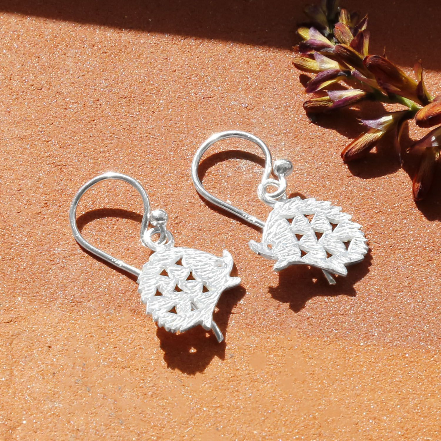 Silver Hedgehog Drop Earrings with a Brick Textured Background With Dried Flowers