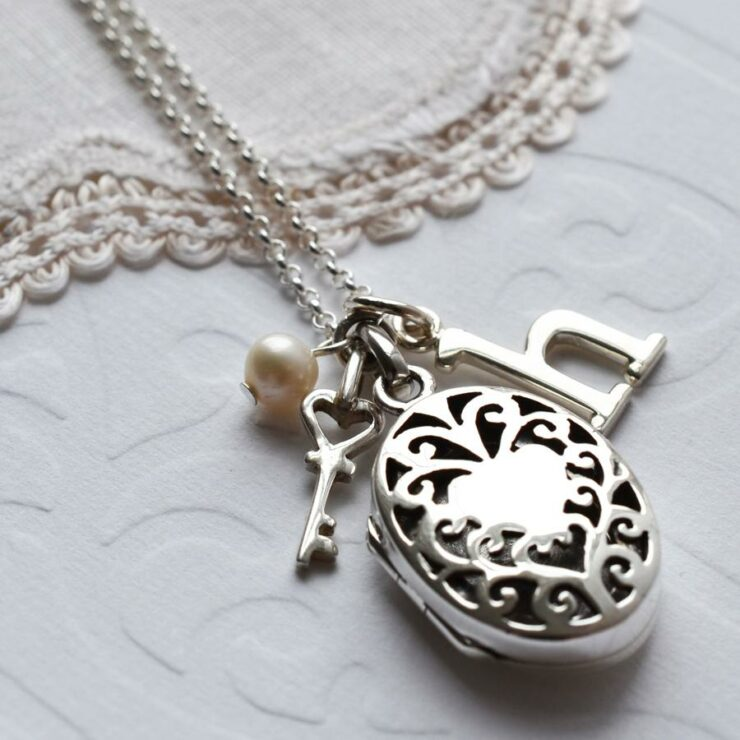 Silver decorative round vintage locket with key, pearl and letter h charm