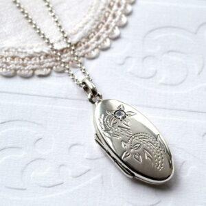 Silver floral oval locket with embedded zirconia gemstone