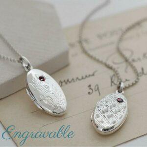 Silver floral oval locket with embedded garnet gemstone