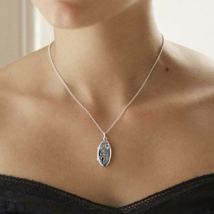 Silver floral oval locket with embedded amethyst gemstone