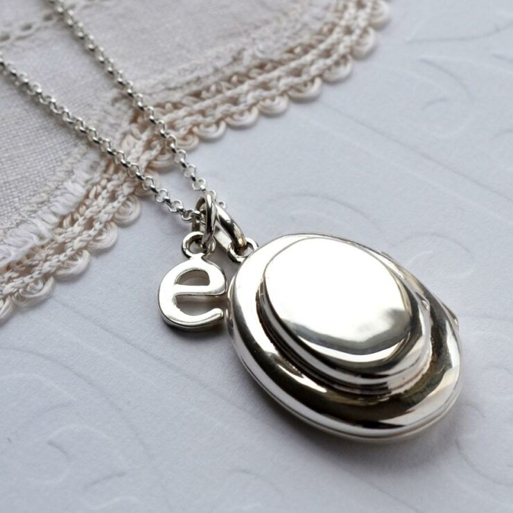 Silver double oval locket holds four photos