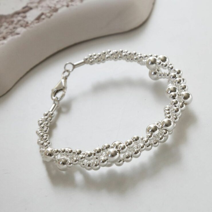A twisted bubble silver bracelet with a lobster clasp lying on a white background with its shadow being cast and grey stone in the background