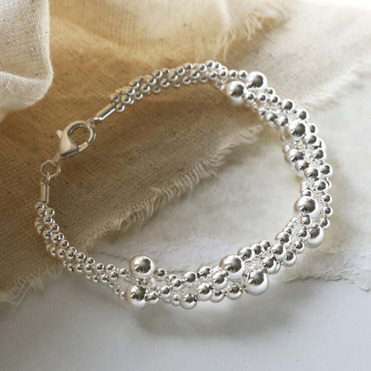 A twisted bubble silver bracelet with a lobster clasp lying on a white background with its shadow being cast and yellowed material in the background