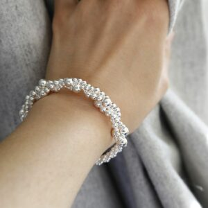 A twisted bubble silver bracelet with a lobster on woman's wrist with a grey background