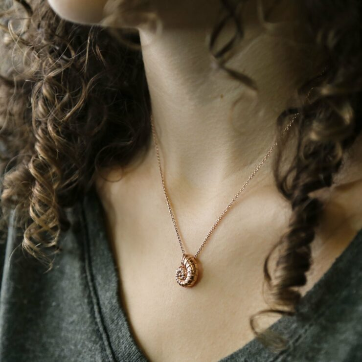 Woman wearing rose gold nautilus shell necklace