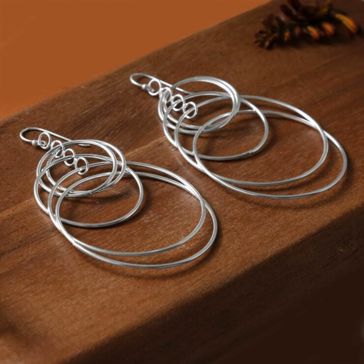 Multiple shiny silver rings hanging on hooks laying on a dark wooden background