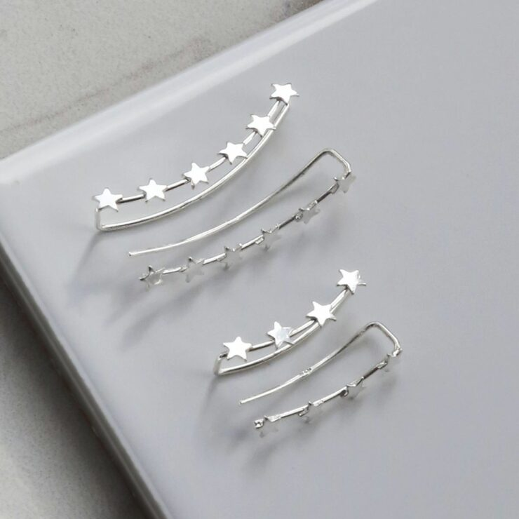 Sterling silver 4 and 6 star ear climbers on a white glossy tile back ground