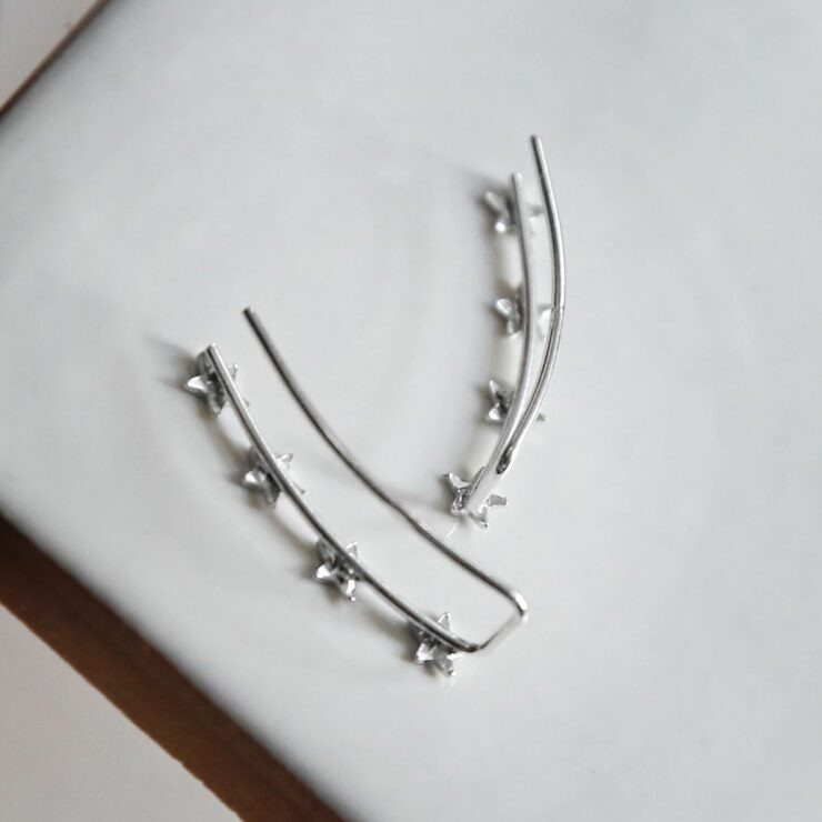 Silver 4 star ear climbers on white background