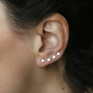 Silver 4 star ear climbers on models ear with black flowing hair