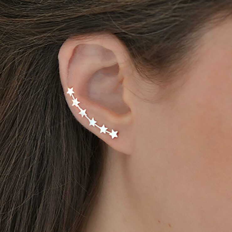 Silver 6 star ear climbers on models ear with brown flowing hair