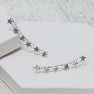 Silver 6 star ear climbers on white plaster hexagon