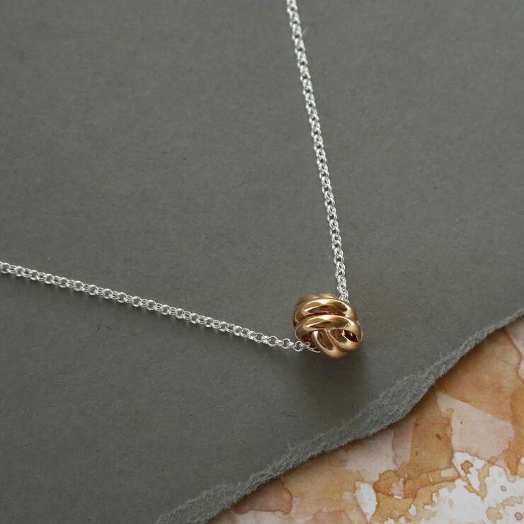 Rose Gold Sterling Silver Forever Knot Necklace on grey background