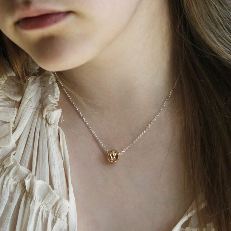 Rose Gold Sterling Silver Forever Knot Necklace on Model with cream top on