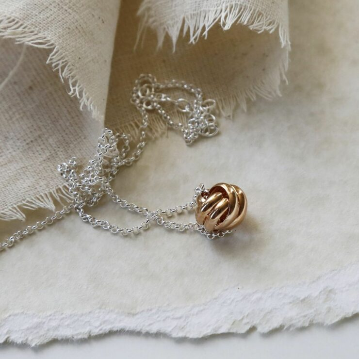 Rose Gold Sterling Silver Forever Knot Necklace on Canvas Background