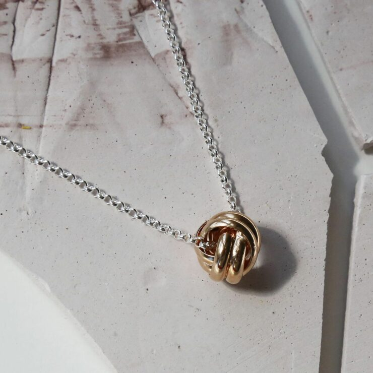 Rose Gold Sterling Silver Forever Knot Necklace on Pale Pink Background