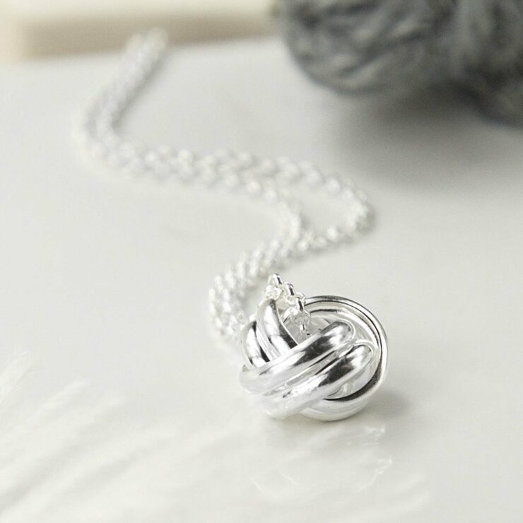 Silver Forever Knot Necklace in focus with Grey Yarn Background