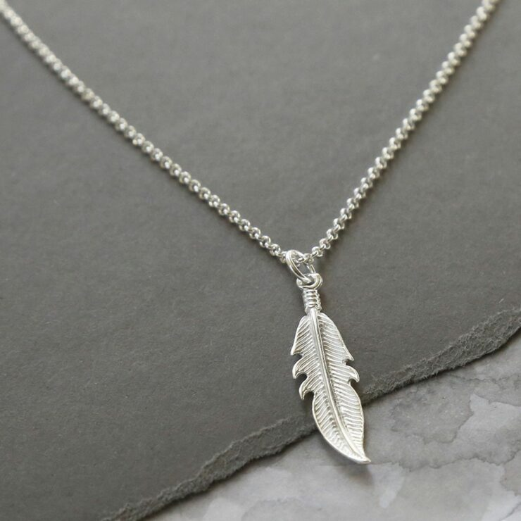 A delicate silver feather pendant hanging from a silver belcher chain over a grey slate
