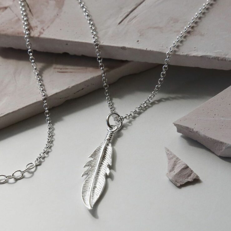 Delicate silver feather hung on a silver belcher chain laying over light brick coloured stone