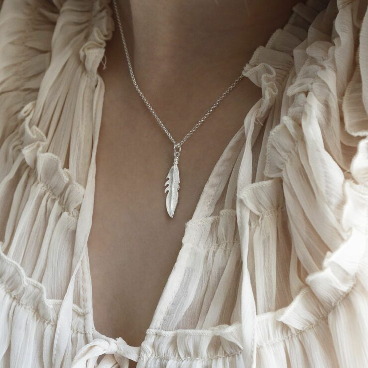 A delicate silver feather pendant hanging from a silver belcher chain round a woman's neck surrounded by white see through material