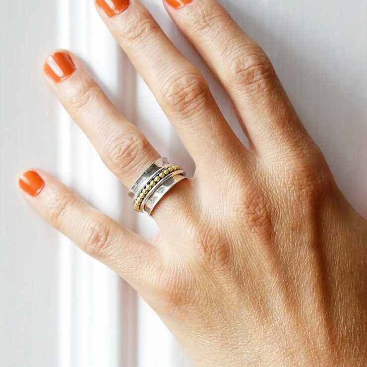 Self care spinning ring with gold detail on model with Orange nail polish against a white wall