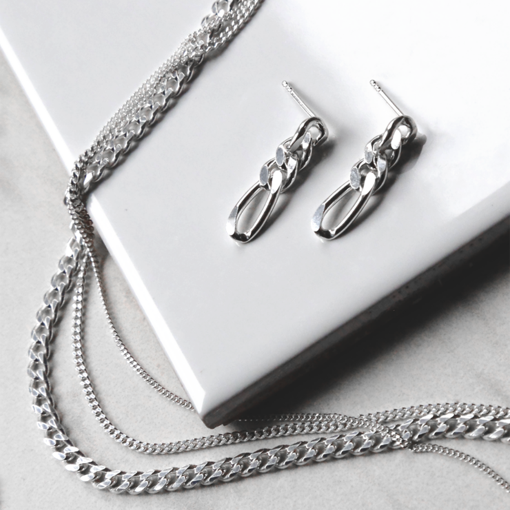 sterling silver figaro chain earrings on white background with multiple chains