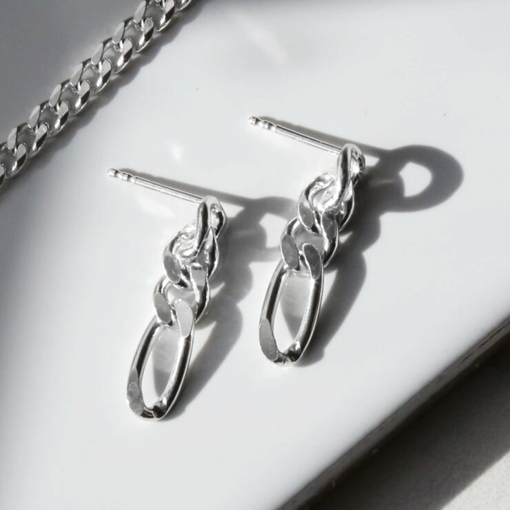 sterling silver figaro chain earrings on white background with chain necklace
