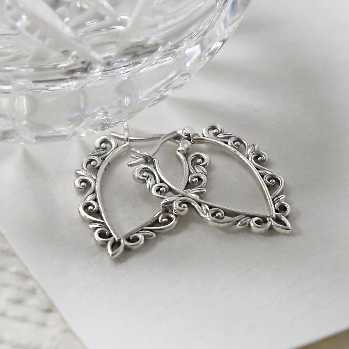Sterling Silver Harmony Hoops interlocked on white background with vase