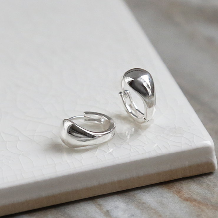Sterling Silver Chunky Huggies on a white background showing one on the side.