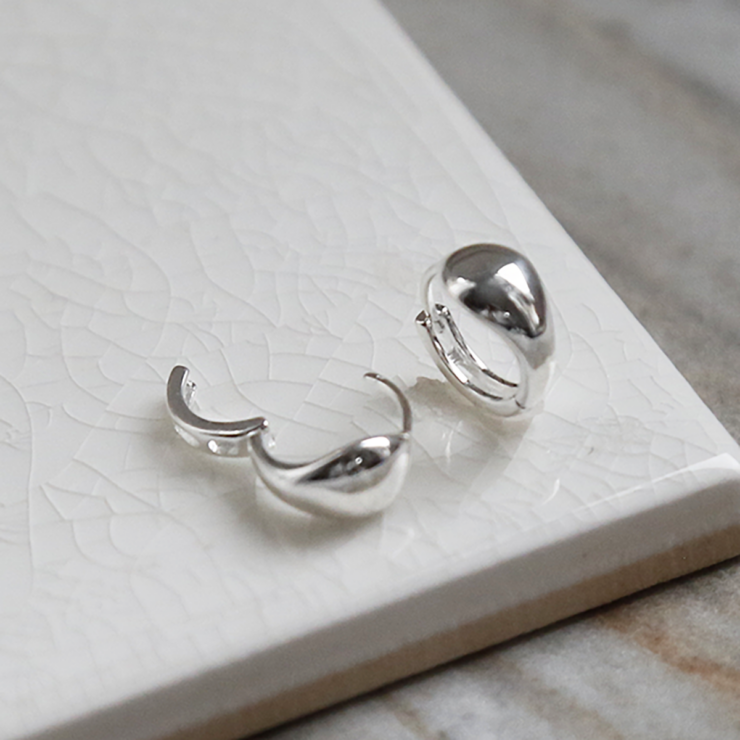 Sterling Silver Chunky Huggies on a white background. One earring open and one closed,