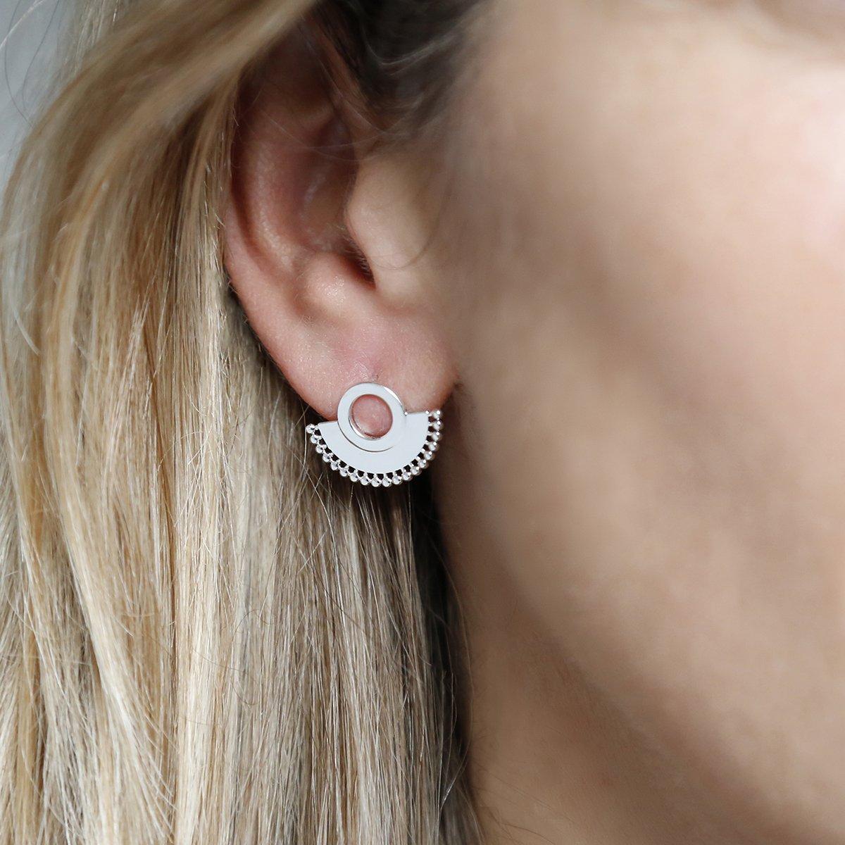 Sterling silver art deco sunburst stud earrings close up on great background on earlobe of model