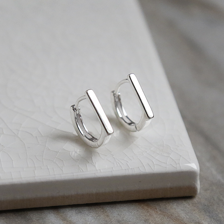 Sterling Silver Straight Edge Huggies on white background.