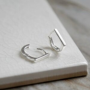 Sterling Silver Straight Edge Huggies on white background. One open and one closed.