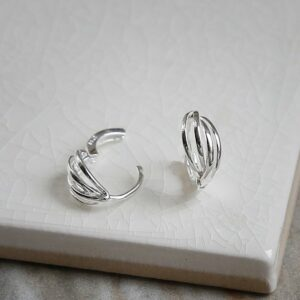 Polished sterling silver braided huggies/ hinged hoop earrings on white background showing one hinged and one un-hinged.