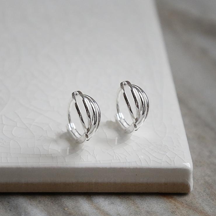 Polished sterling silver braided huggies/ hinged hoop earrings on white background.