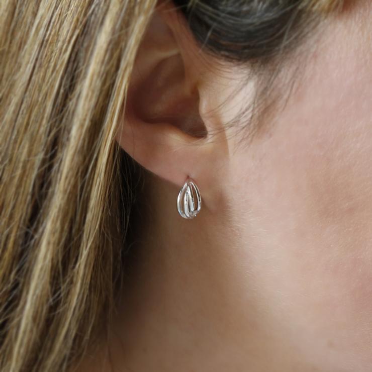 Polished sterling silver braided huggies/ hinged hoop earrings on model's ear.