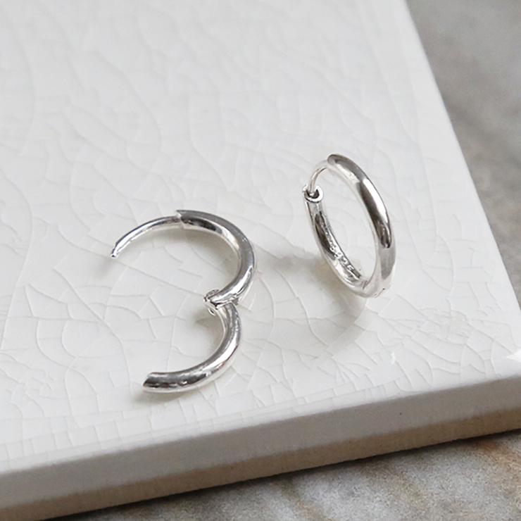 Big sterling silver huggies on white background, one open and one closed.